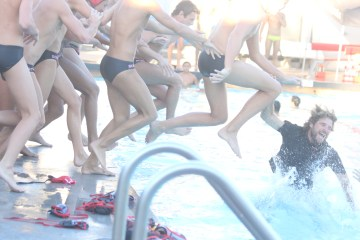 San Clemente High School boys water polo coach Logan Powell jumps into the pool to celebrate the Tritons' first league title since 2009. Photo: Eric Heinz