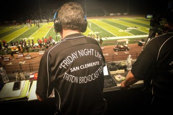 Richard Corder, in his Friday Night Live branded shirt, has been the play-by-play man for all 15 years of broadcasts. Photo: Eric Heinz