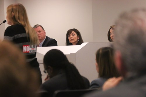 """Councilmember Laura Ferguson, center, listens to a public speaker with a """"No Toll Road"""" sticker on her back on Thursday, March 14, at a TCA joint board meeting in Irvine. Photo: Eric Heinz"""