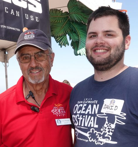 David Vaughn, right, has volunteered for eight years at the San Clemente Ocean Festival, five of those years while serving at Camp Pendleton. Now in business, he flew in from Ohio to volunteer this year, staying at the home of fellow volunteer Ernie Marquez, left. Photo: Fred Swegles