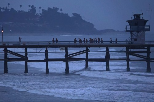 As night turns to day, the Pier to Pier Quest begins on the end of the San Clemente Pier with a run toward shore. Photo: Fred Swegles