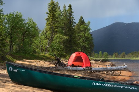 Canoe and Hilleberg Anjan 3 on a riverbank in Lapland.