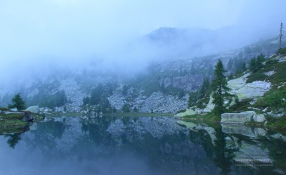 Tranquil lake in Ticino during a foggy morning.