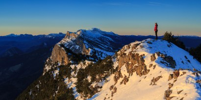 Female hiker in the snow covered Vercors looking at the sunrise.