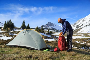 Packing my backpack after camping in the mountains during springtime.