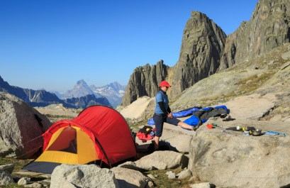 Young woman stretching at a campsite high in the mountains.