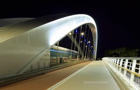 The Raymond Barre bridge with a tram speeding over it.