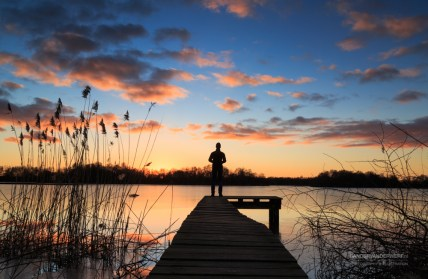 Man standing on a small jetty, enjoying the winter sunset over a lake.
