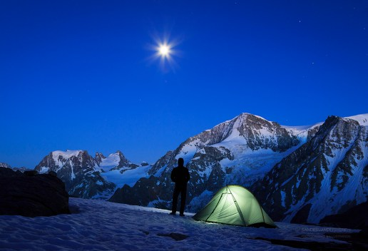 Mountaineer and tent, looking at the moon rising above the mountains in Wallis.