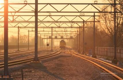 Passenger train and railroad tracks during a nice sunrise.