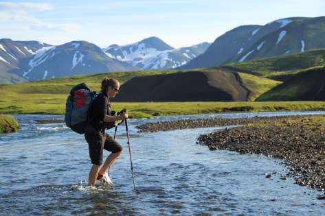 Female hiker crossing a river on the Laugavegur trail.