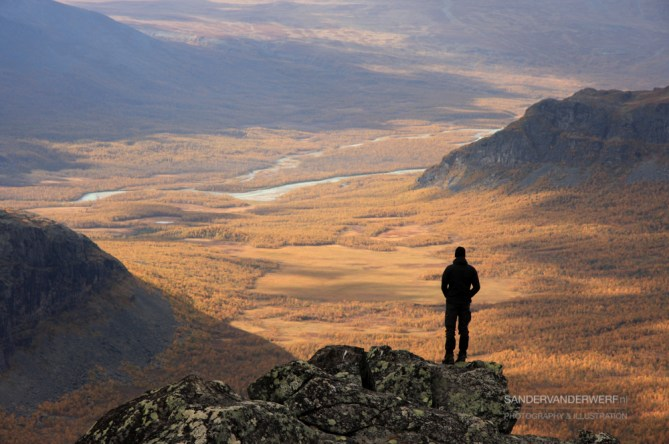 Man looking at a valley with autumn colors.
