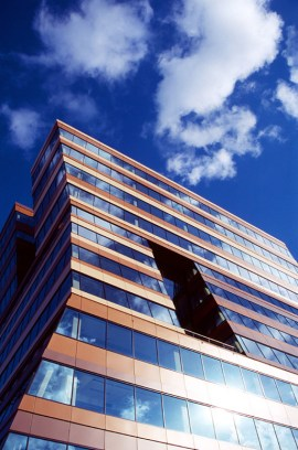 Menzis building with a blue sky and white clouds.