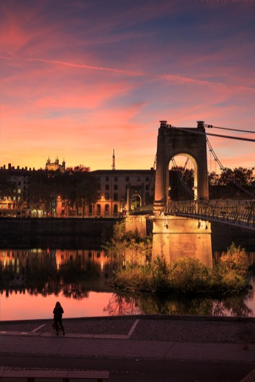 Sunset at the iluminated Passerelle du College over the Rhone river in Lyon, France.