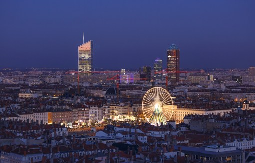 Ferris wheel with smiley on Place Bellecour during twilight.