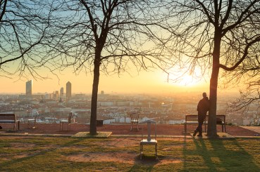 Man in a park enjoying the sunrise over the city.