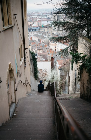 Man sitting in a steep alley in Vieux-Lyon.