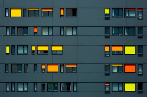 Black facade of a modern building with colorful blinds.
