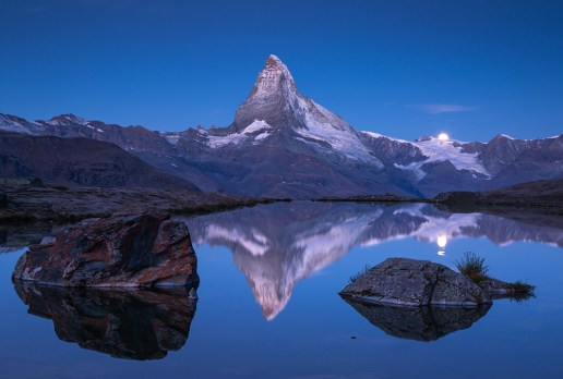 The famous Matterhorn and the moon reflected in the Stellisee before dawn. Zermatt, Switzerland.