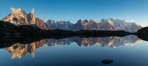 Panorama of the Mont Blanc massif reflected in Lac de Chesery during sunset.