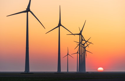 Sunset at a row of modern wind turbines generating sustainable energy.