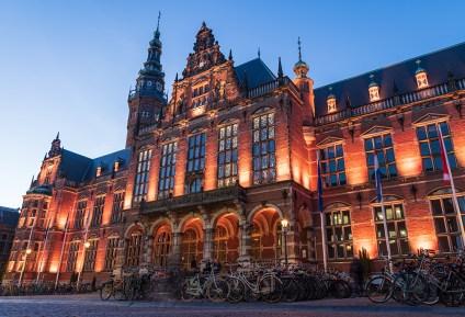 Academy building of the University of Groningen illuminated at night.