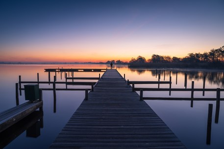 Man on a jetty enjoying a tranquil dawn at the Leekstermeer.