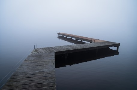 Wooden jetty in a lake, on a foggy, winter morning.