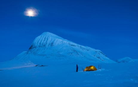 Hiker and her tent in the snow covered moiuntains of Sarek, in Swedish Lapland.