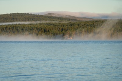 Remote cabin in the fog on the shore of a lake. Jamtland.