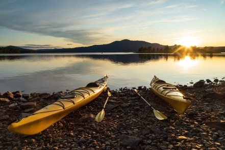 Two kayaks on the shore of a lake during a tranquil sunset. Jamtland.
