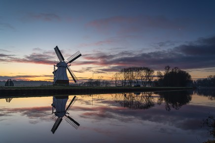 Foggy, winter dawn at a windmill reflected in a canal.