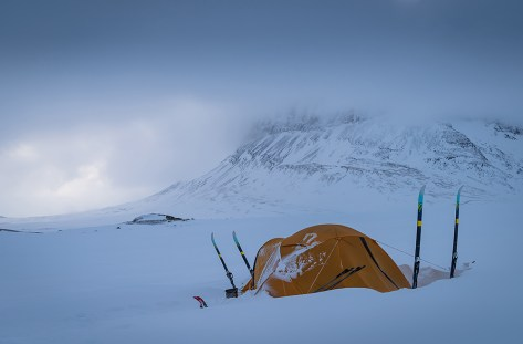 Tent in the snow on a cloudy morning in Lapland. Sarek, Sweden.