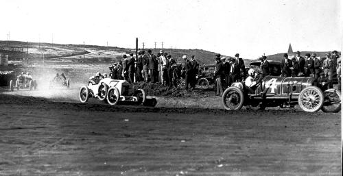 The fastest racers in the world making a turn on the dirt track at Point Loma.