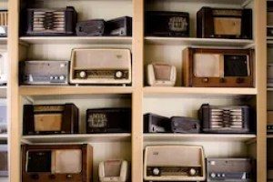 Listen: old radio sets on a wooden shelf