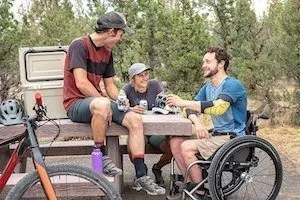 Inclusive marketing - Young man in wheelchair shares beers with man and woman at picnic table