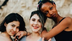 Three young women of different ethnicities smiling together