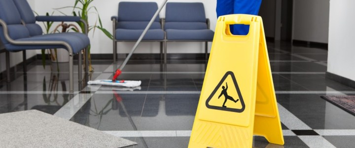 Working janitor with slippery sign
