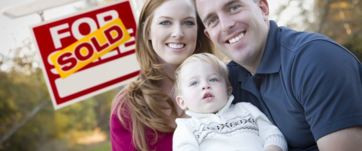 couple with baby in front of sold real estate sign