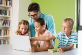 photo of three students in front of a laptop with their teacher