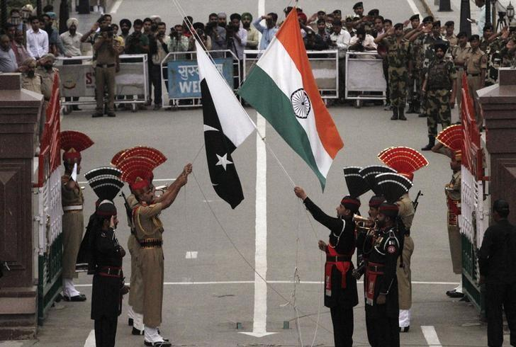 Pakistani rangers (wearing black uniforms) and Indian Border Security Force (BSF) officers lower their national flags during a daily parade at the Pakistan-India joint check-post at Wagah border, near Lahore November 3, 2014. REUTERS/Mohsin Raza/Files