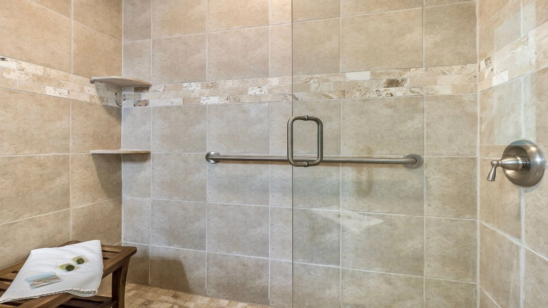 Master shower with seating area.