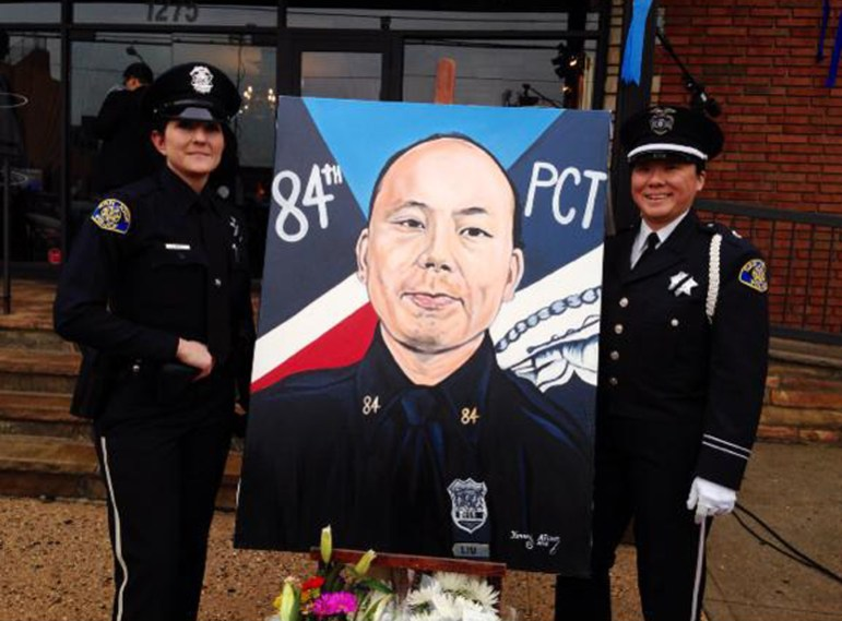 San Jose police officer Wakana Okuma, right, poses with an image of slain New York City officer Wenjian Liu at a funeral in January. SJPD Chief Larry Esquivel posted the image to his Twitter account. (Photo via Twitter)