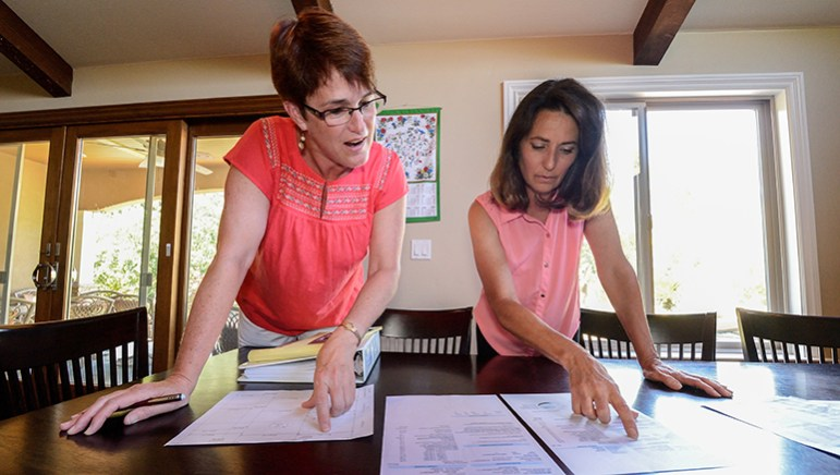 Ginny Hoerger (left) and Rita Benton pore over water bills and other records. (Photo by Greg Ramar)