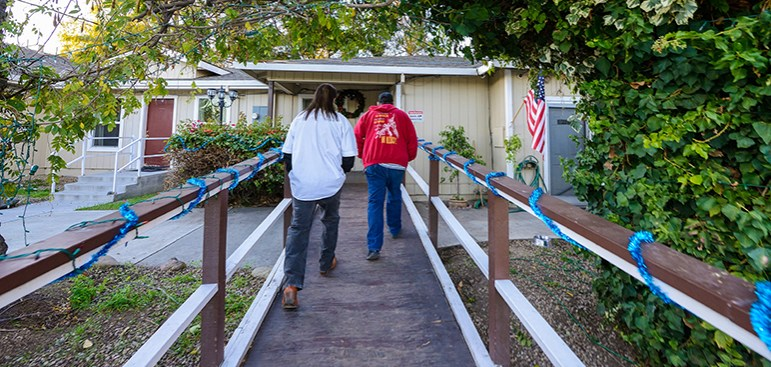 Richard Franko and counselor Joaquin Aguirre (left to right) walk up the ramp to Life Choices, a former drug treatment facility that has since become an unlicensed sober living home. (Photo by Greg Ramar)
