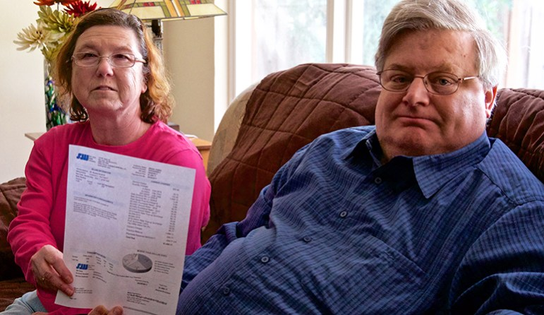 Brian and Aimee Jones with their $1,696 water bill from September 2017 in their San Jose home. (Photo by Kevin N. Hume)