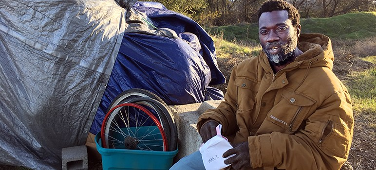 Sharwian Bobian sits outside his makeshift shelter.