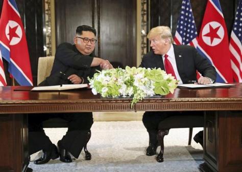 共同声明の署名式で握手する北朝鮮の金正恩朝鮮労働党委員長(左)とトランプ米大統領=12日、シンガポール(ロイター)