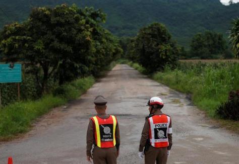洞窟への道を封鎖しているタイの警察官=8日、チェンライ(ロイター)