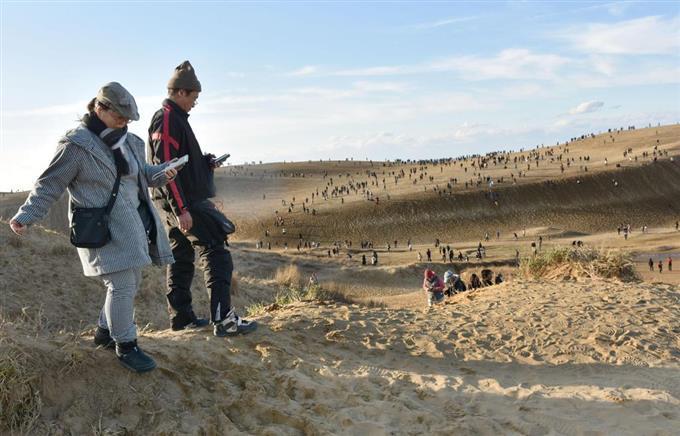 鳥取砂丘で「ポケモンGO(ゴー)」を楽しむ人たち=25日午後